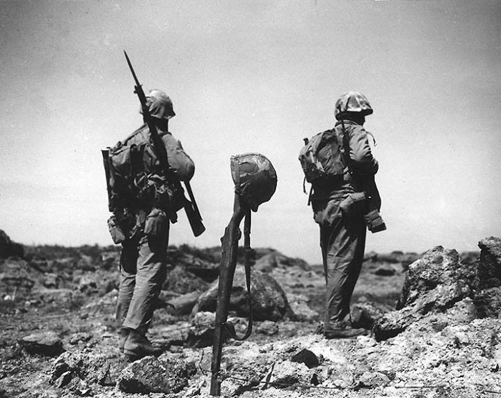 Two Americans walked by a temporary grave of a fellow Marine made of the fallen's rifle and helmet February 1945.