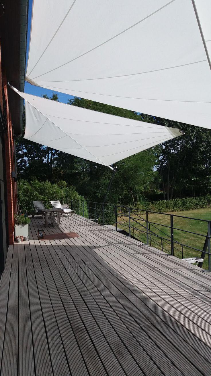 Oprolbaar design zonnezeil te Mol. Masten tegen verhoogd terras met zeilboot design afgewerkt door Horpirol