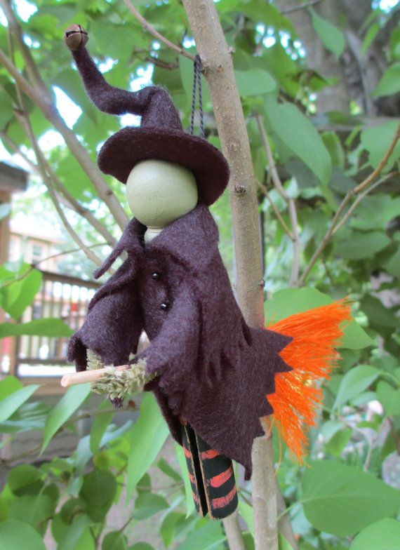 ModerationCorner on Etsy A new character for us in 2014, this wicked looking witch rides on her straw broom. She is created from a clothespin, wood ball, pipe cleaner and scraps of wool felt. She wears a dress and cloak of black wool felt, with a matching twisted hat with jingle bell. The broom is attached through the clothespin, and her hands wrap around it to mimic a flying witch.