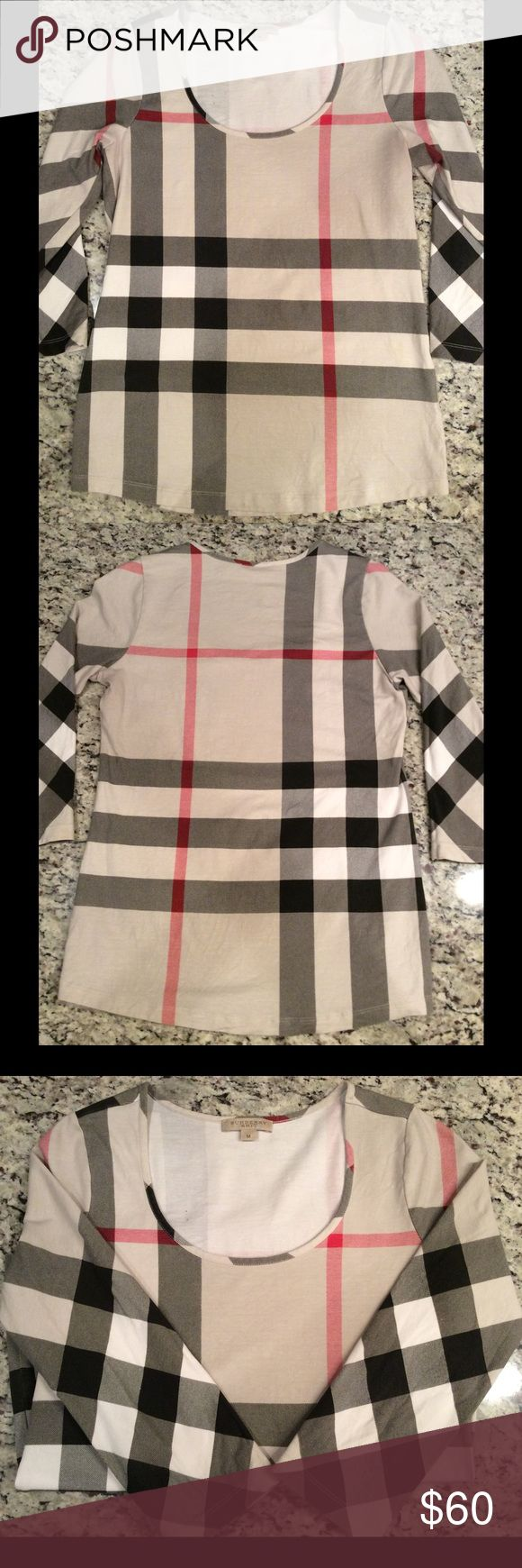 "-Burberry Brit- 3/4 Sleeve original Checker Sz M Used, but good condition! Care tag has fading. There are 2 small dots on the -Inside of shirt on back right shoulder. (See pictures). Can't be seen from outside. Fitted and has a nice stretch. 95% cotton, 5% elastin. Shoulder to hem 22"" armpit to armpit 15"" sleeve 24"" Tops"