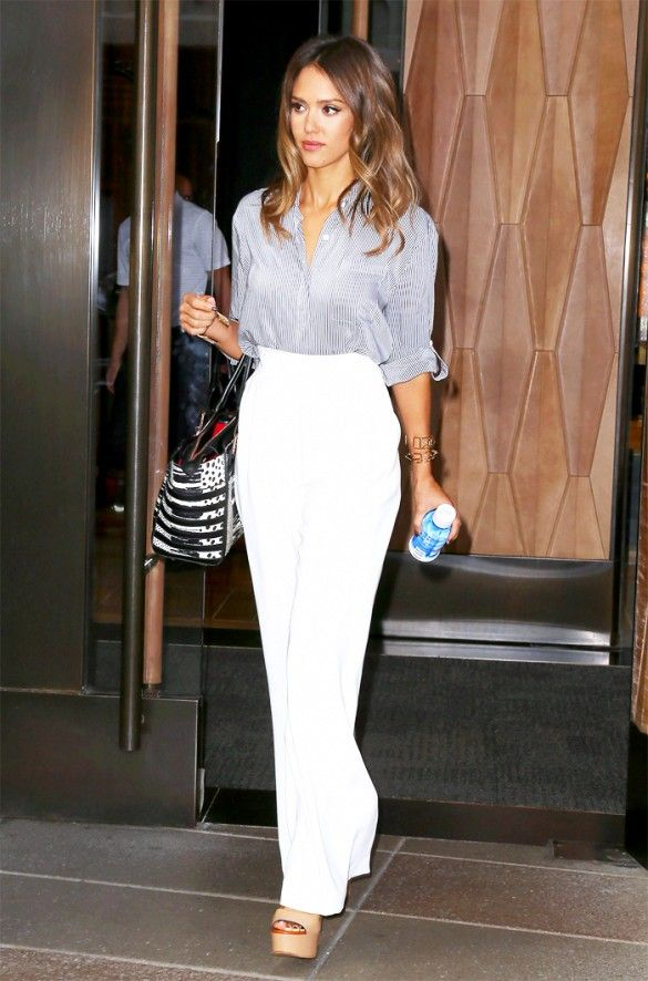 Jessica Alba wears a striped button-down blouse tucked into white high-waisted trousers with platform sandals