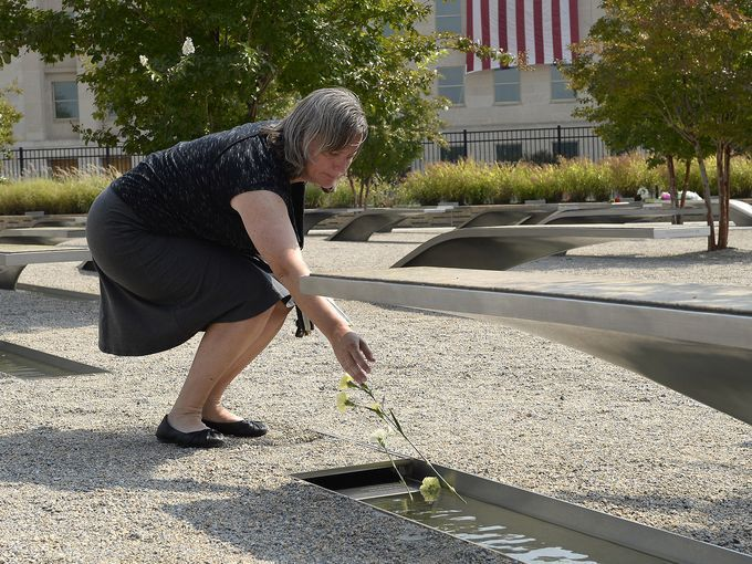 Laura Tayloe places flowers at a memorial bench dedicated to a victim of a Sept. 11, 2001, terrorist attack at the Pentagon 9/11 Memorial in Arlington, Va.