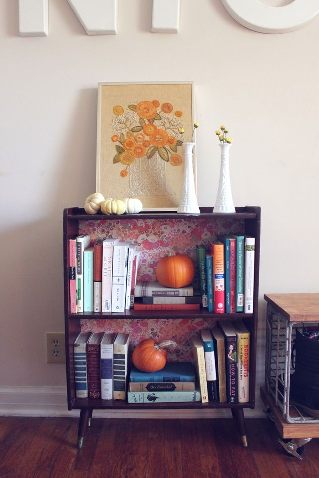 love the wallpaper on the back of this bookcase, the pumpkin peeking out among the books, & the lovely framed embroidery; home of Rachel Denbow, from Smile & Wave blog