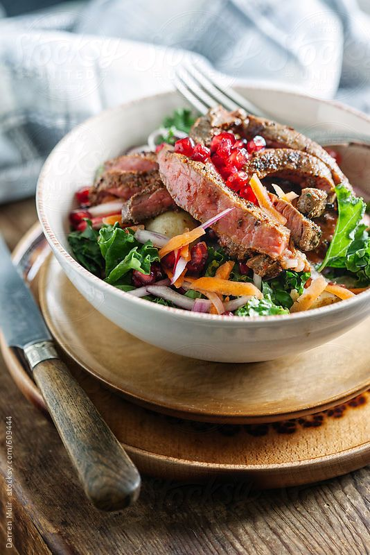 Steak salad in a bowl,closeup in table setting. by DarrenMuir | Stocksy United
