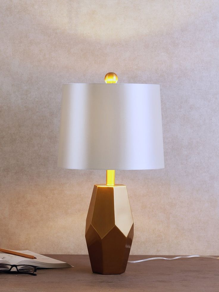 Penta striking with modern flair the penta table lamp sits on a gold base