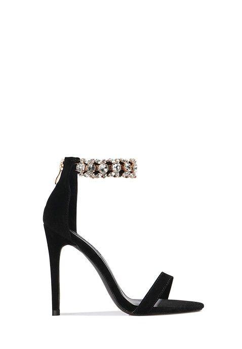Cette sandale noire à talon aiguille affiche une jolie ligne et de très jolis détails sexy et glamour. L'arrière du pied est recouvert et relié au tour de cheville avec fermoir, présentant des détails métalliques chic. Une fine lanière maintient les doigts de pied à l'avant.