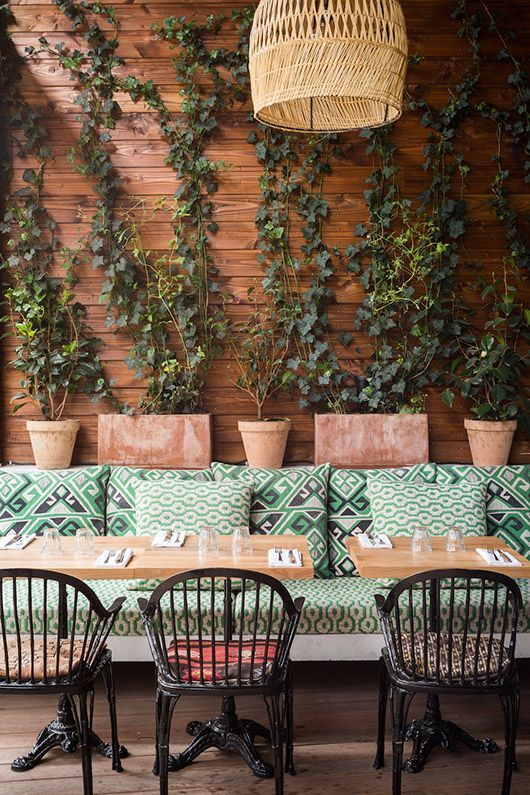 Loving the shades of green in this boho outdoor restaurant patio space. Looks great accented with black, terra cotta and rattan.