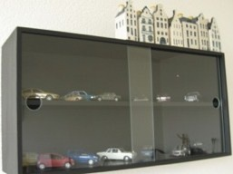 De vitrinekast is zwart geverfd en staat vol modellen auto's die we in het bezit gehad hebben.