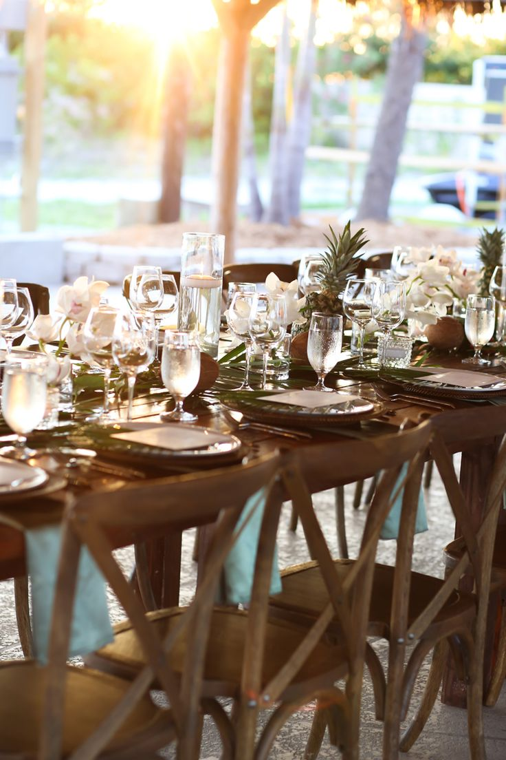 Tropical beach wedding reception tablescape with pineapples and orchids and vineyard chairs (Lifelong Photography Studio)
