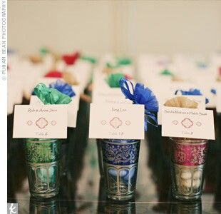 Morocan glasses are used to display escort cards at a wedding reception. Glasses are filled with Jordan almonds.