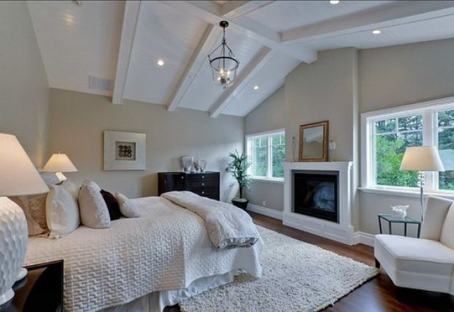 Benjamin Moore Grant Beige shown in what looks to be a north facing master bedroom with fireplacec and neutral accents and linens