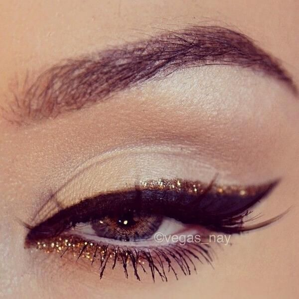 Eye makeup with black cat eye liner and gold glitter accents