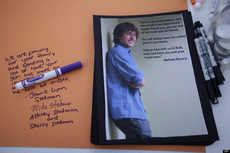 A tribute to movie theater shooting victim AJ Boik, is shown along with his photo, on a message table Saturday, July 21, 2012, at a vigil at Gateway High School in Aurora, Colo., Boik, was a student at the school and was killed along with 11 others when a gunman opened fire in a movie theater.