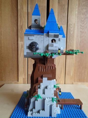 Ein kleines Schloss auf einem Riesenbaum im Meer. Es besitzt einen Aussichtspunkt mit Fernrohr, Laternen und einen Bootssteg. Im Schloss befindet sich eine kleine Kapelle mit Glockenturm auf dem Dach. In der Mitte des Schlosses wächst ein Baum.   Ich hoffe dir gefällt mein Modell :)