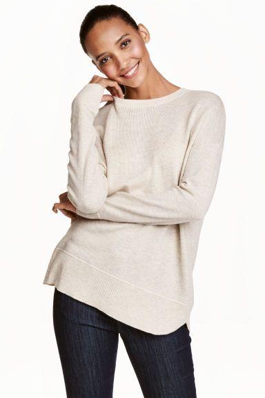 Camisola em malha fina: Camisola em malha fina e macia com uma percentagem de lã. Tem ombros descaídos, mangas compridas e fecho éclair visível nas costas. Punhos e cós em malha canelada.