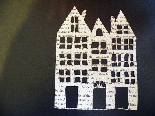 Paper houses cut from book pages or newspaper for wall picture arrangement.