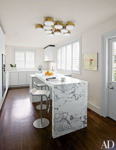 A midcentury light fixture by Gio Ponti is positioned above a Boffi breakfast bar and stools from Design Within Reach in the kitchen of a London rowhouse decorated by Veere Grenney.