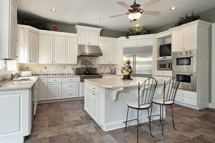 U-shaped white kitchen with white counter tops on darker neutral toned tiles with stainless steel appliances