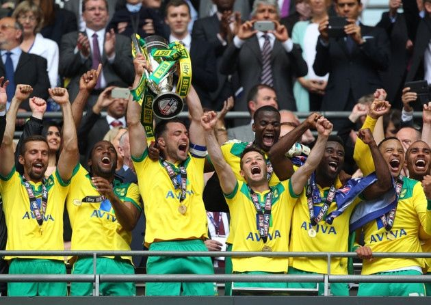 Norwich City captain Russell Martin lifts the Championship play-off trophy after a 2-0 Wembley win secured promotion for the Canaries.