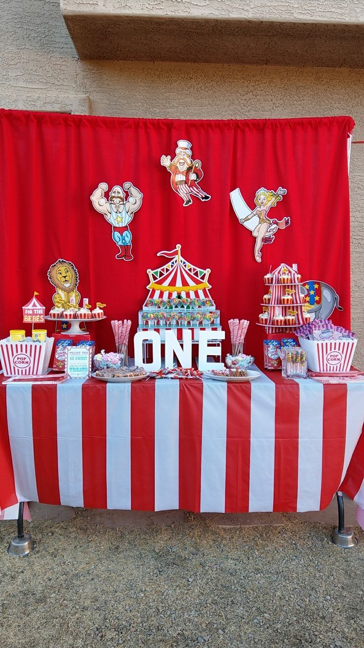 Carnival treat table. DIY backdrop using red fabric and 3/4 PVC. Decoratuins from Oriental Trading, containers from Dollar Tree Circus Carnival theme 1st birthday party