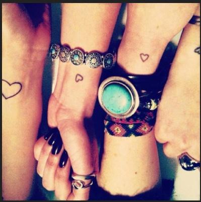 Friends matching heart tattoos.