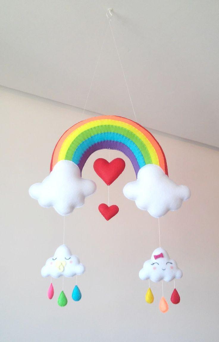 Móbile feito de feltro, costurado a mão e preenchido com fibra siliconada.    Lindo móbile composto por um arco-íris, nuvens fofinhas e corações. Sua leveza, o seu colorido e mobilidade traz calma e distração para o seu bebê.    Deixa qualquer ambiente alegre e divertido.    Medidas Aproximadas: ...