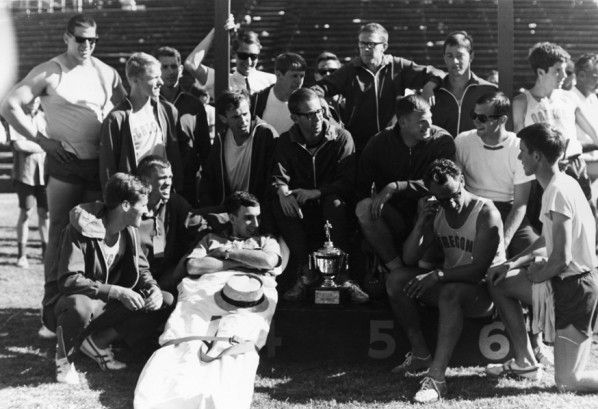 Black and white photo of members of the 1966 University of Oregon track and field team gathered around their third-place trophy at the Pac 8 Conference championships held in Stanford, California. ©University of Oregon Libraries - Special Collections and University Archives