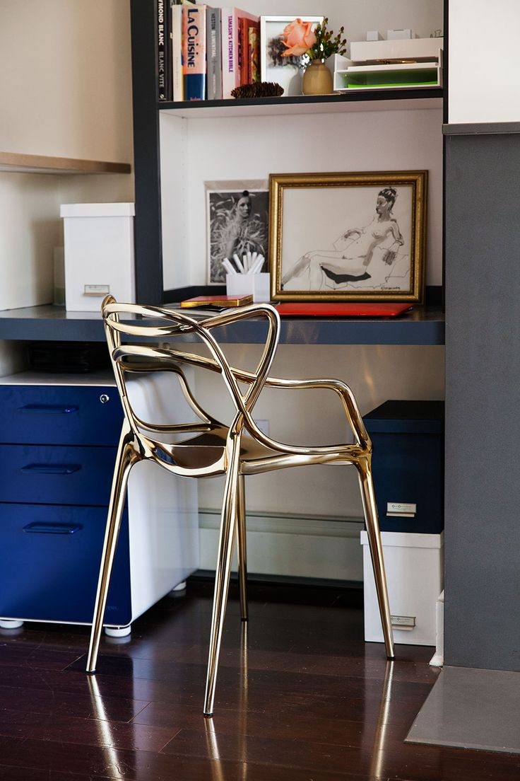 A sleek gold Kartell chair elevates a minimal corner work space
