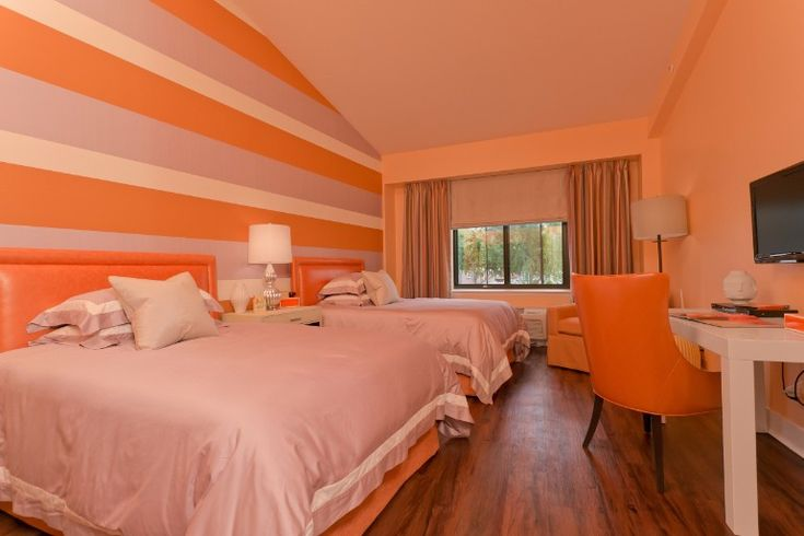 Bedroom with total orange madness on this pretty design with stripy wallpaper and a modern chair and desk combo. Simplicity can be fun too.