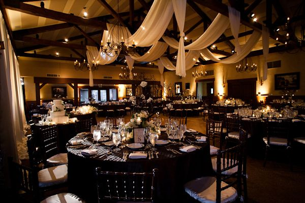 Beautiful indoor reception seating area - Black chairs with ivory cushions, black tablecloths with ivory napkins, and white, ivory, and green floral centerpieces with ivory chiffon draped from ceiling and black chandeliers with warm lighting - wedding photo by Michael Norwood Photography