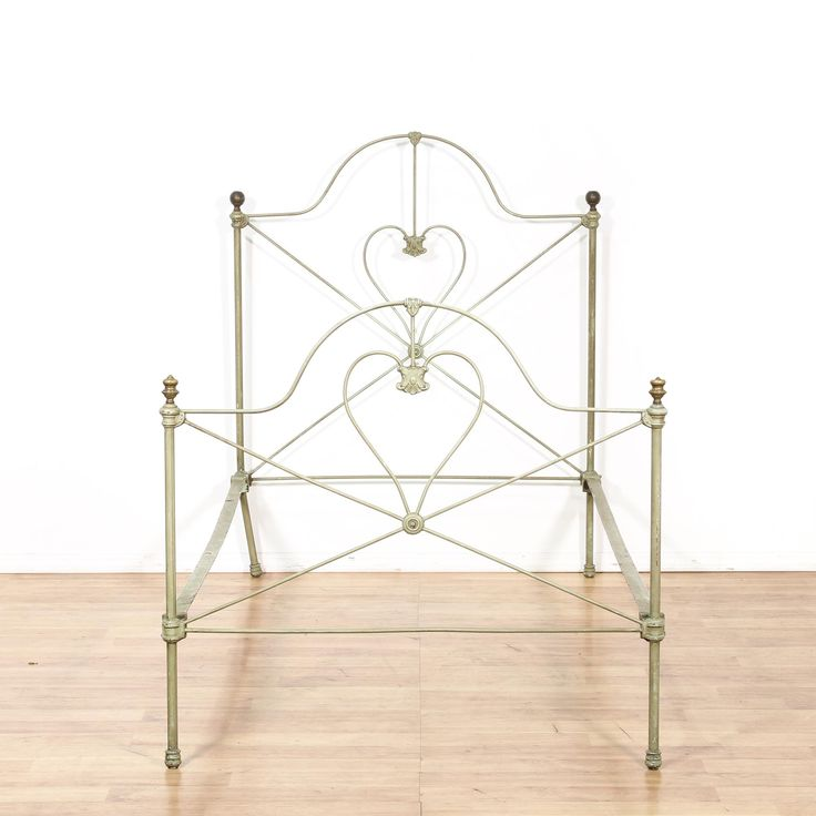 This shabby chic bed frame is featured in a durable metal with a distressed off white finish. This twin sized bed has curved tops with finial columns and heart accents. Adorable bed perfect for a small bedroom! #shabbychic #beds #bedframe #sandiegovintage #vintagefurniture