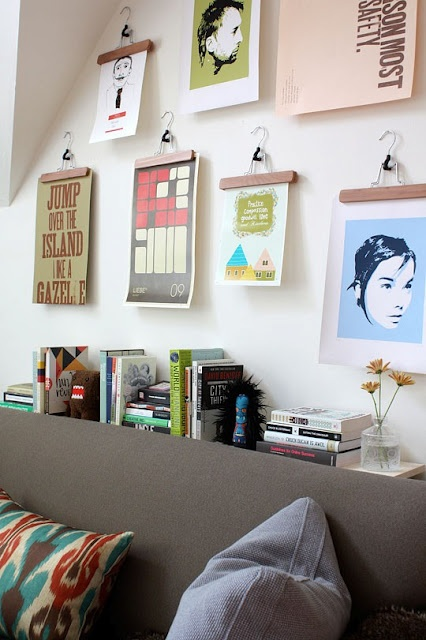 Love the idea of hanging prints with hangers and having a library table behind the couch!