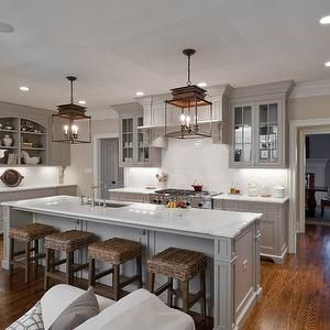 Medium tone greige cabinets, wood floor, white counters and back splash. Bronze light fixture, bar stools, cabinet hardware act as a chocolate accent.