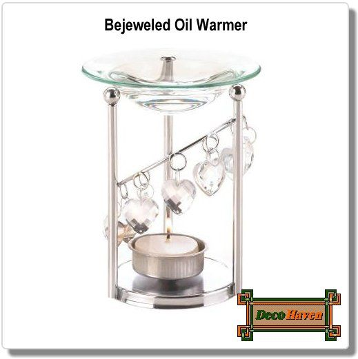 Bejeweled Oil Warmer - Let your love of fantastic aroma fill your living space! This sparkling oil warmer features an iron frame with dangling faceted heart jewels. Add the scented oil of your choice to the glass basin and your favorite tealight candle below.