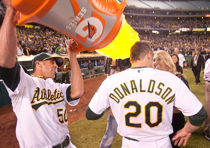Oakland Athletics' Grant Balfour, left, dumps the Gatorade bucket on teammate Josh Donaldson after the A's completed a come-from-behind win over the Detroit Tigers in Game 4 of their American League Division Series, Wednesday, Oct. 10, 2012, at O.co Coliseum in Oakland, Calif. The A's won, 4-3. (D. Ross Cameron/Staff)