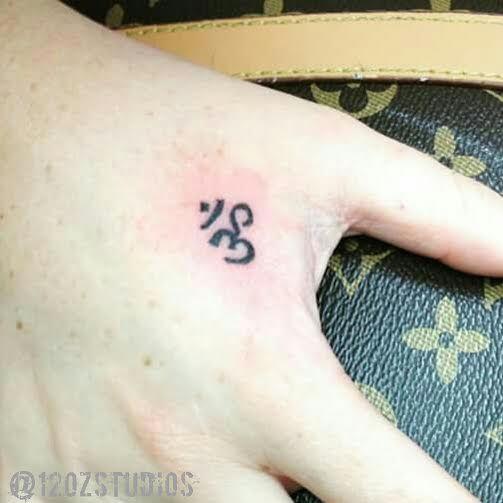 Small dainty delicate black ohm symbol female hand tattoo by Alex Feliciano.