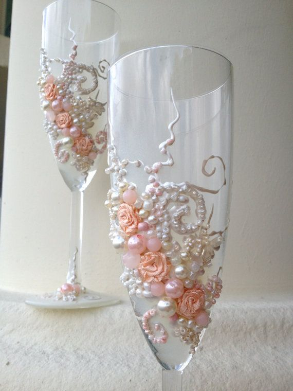 Beautiful wedding champagne glasses in blush pink and ivory, elegant toasting flutes with pearls and roses