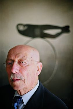 Enrico Taglietti, 2007 RAIA Gold Medallist. The background image shows a work by sculptor Rod Dudley. Part of a poster from the Bonythorn Gallery, 1973. Photograph Vikky Wilkes.