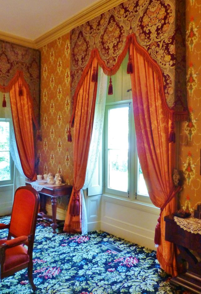 The dining room windows feature silk draperies with ornate damask lambrequins. A lambrequin is an upholstered cornice board which extends f...