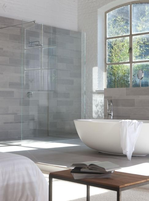 Beautiful gray tile laid brick-style with a glass shower and large tub