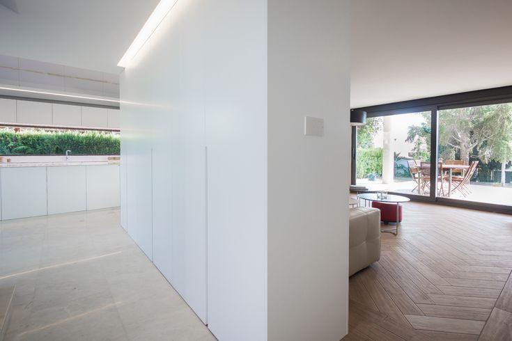 Armariada blanca que divide el espacio de la entrada del moderno comedor salón abierto | Chiralt Arquitectos | Valencia