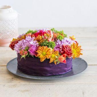 Een vrolijke taart gevuld met kleurrijke bloemen. Geweldig leuk voor bij een high tea buffet met vriendinnen. Daar maak je vast de blits mee! De anjers, chrysanten en Craspedia's zijn lang houdbaar, waardoor de taart lang plezier geeft!