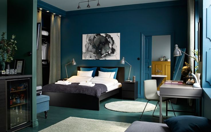 A medium sized bedroom furnished with a black-brown bed for two combined with chest of drawers used as bedside tables.