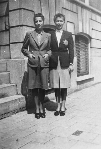 Two sisters, Jetty and Shelly de Leeuw, pose on the street wearing Jewish badges in the Ghetto of Amsterdam. Both were later deported and perished in concentration camps.