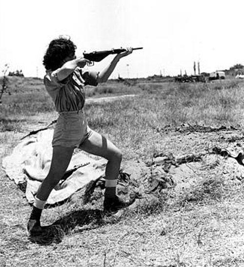 Un ufficiale donna a capo del campo al campo corpo delle donne Hen vicino a Tel Aviv, la Palestina, dà una dimostrazione nella gestione di una pistola Sten il 15 giugno 1948 nella guerra arabo-israeliana. Anche se non combattenti, Esercito membri delle nuove donne in Israele viene insegnato ad usare le armi per la difesa. (AP Photo / Public Domain)