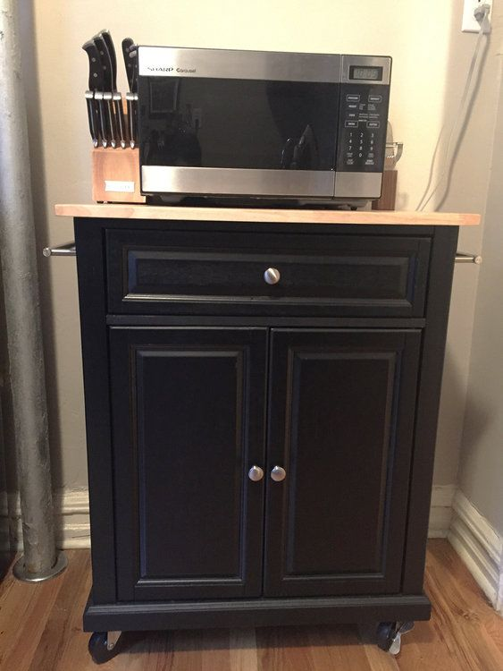 A mobile kitchen island / microwave cart: the cabinet is black, made with a mix of solid hardwood with veneer, and the top is solid wood with a natural/blonde finish and brushed nickel hardware.