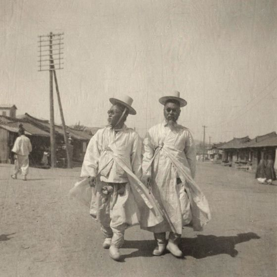 Two well-to-do men, wearing sun glasses, walk through a small Korean town ca. 1904.