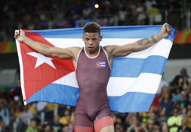 リオデジャネイロ五輪、レスリング・グレコローマン男子59キロ級で金メダルを獲得し、キューバ国旗を掲げて喜ぶイスマエル・ボレロモリナ(2016年8月14日撮影)。(c)AFP/Jack GUEZ