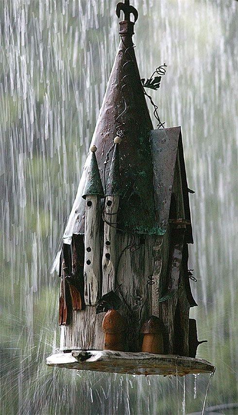 Castle-like birdhouse hanging in the rain