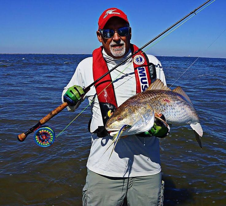 Cradling a nice bull redfish on the fly redfish for Saltwater fly fishing